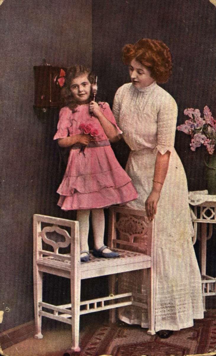 Postkort. Jule- og nyttårshilsen. Fotografisk motiv. Portrett av kvinne og liten pike med telefon. Stemplet 2012.1903.