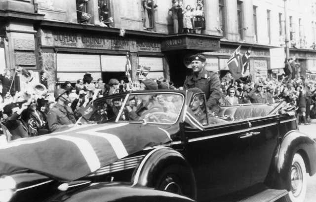 Fra Oslo under fredsdagene i 1945. Den 13.mai kommer Kronprins Olav tilbake. Kortesjen kjører oppover Karl Johans gate i retning Slottet.Kronprinsen sitter på kalesjen og hilser til de fremmøtte.