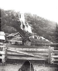 Tvindefoss, Tvinde, Voss. Jorder, gjerder og gårdshus foran.
