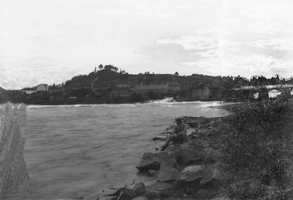 En mann sitter på en sten og skuer ut over elven ved Hønefoss.