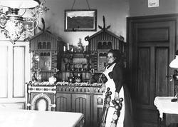 Interiør, kvinne i hvitt forkle i spisestue.