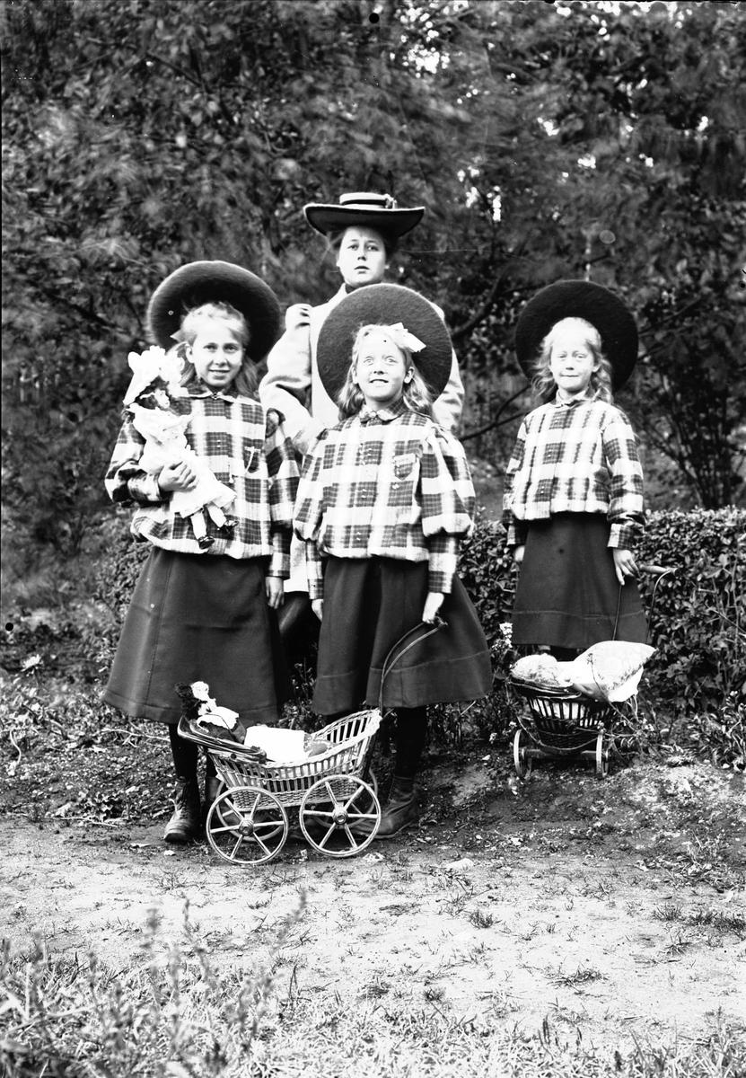 Tre Småjenter I Like Hatter Skjørt Og Ytterjakke Med Dukker Og