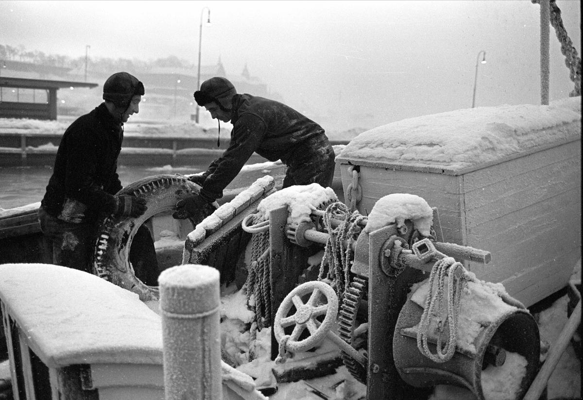 Kaldt på brygga, utstikker C, Oslo, januar 1963. Menn i nediset båt.