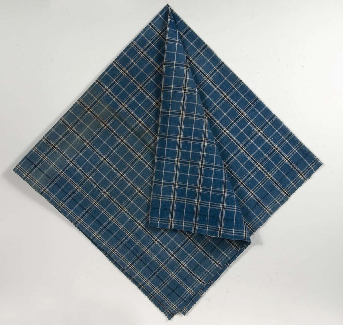 Kläde av bomullslärft. Varp och inslag av blått, mörkblått och vitt bomullsgarn. Rutmönster. Smala fållar på två sidor. Handvävd.