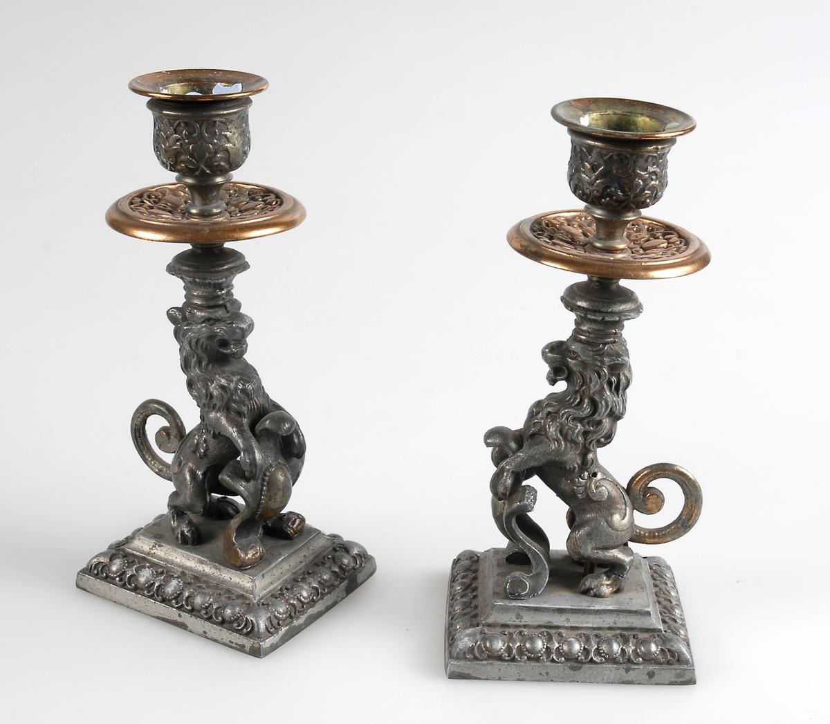 Två ljusstakar av järn med bronserad pipa och manschett. Bronsfärg även på lejonets svans och man, samt på vapnet mellan framfötterna. För övrigt målad i silverfärg.