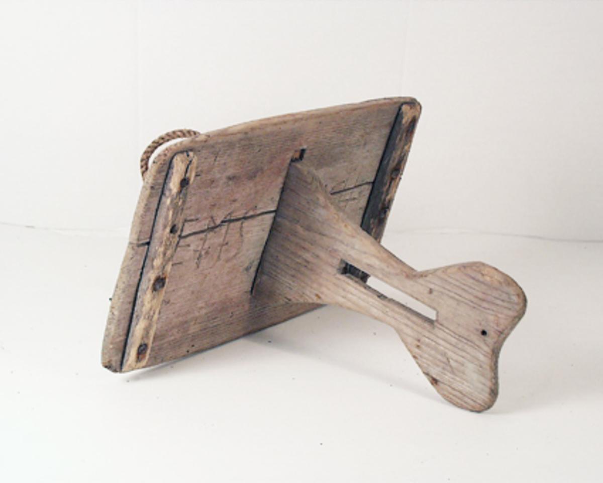 Våla, flöte för strömmingsskötar, av trä. Rektangulär skiva med slå rakt igenom skivan. På skivan inristat: EMS 1846. På den över vattnet uppstickande slån ett bomärke.