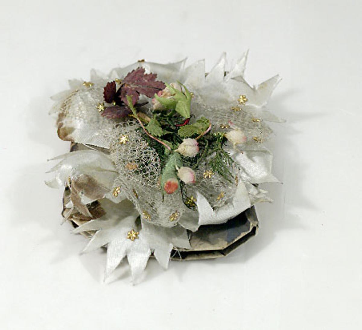 Bröllopskaramell, omslag av silverpapper. Vit tyll, rosa blommor, gröna blad, vita sidenband.