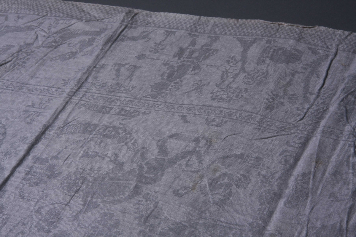 Hvit lindamask med sjakkbrettbord  på begge langsider. Innenfor en bord med jegere til fots, hunder og vilt.På kortsidene ryttere, og i to av hjørnene et slott. Midtpartiet opptaes av båndlignenede ranker som går ut fra et firkantet felt midt på servietten, båret av to flyvende puttier. Mellom rankene Pan og puttier. Smal fall på kortsidene.
