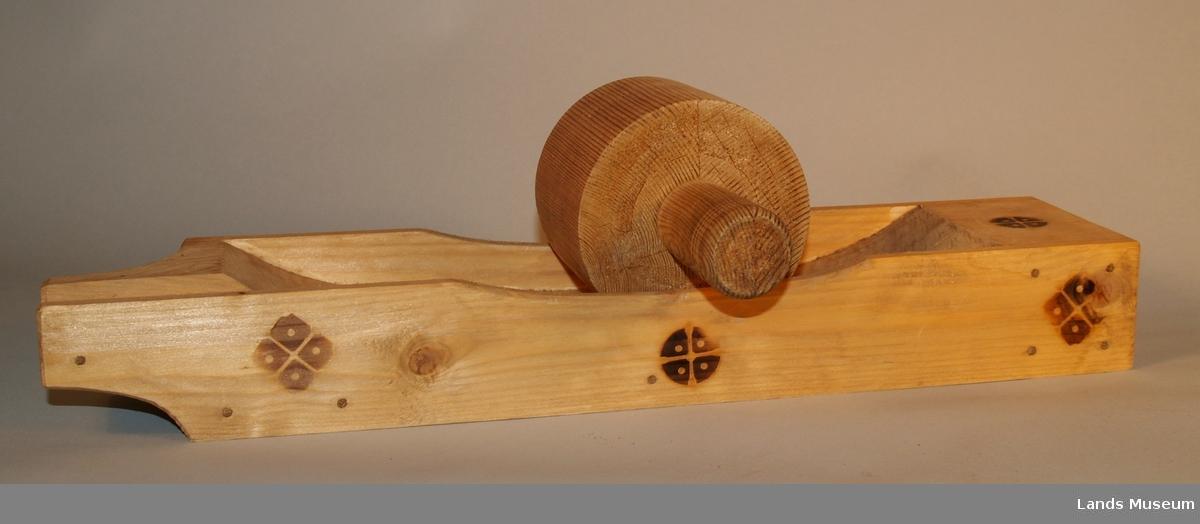 Kaffenú med knuser. Den har ein tut for helling av kaffen. Dekorert med sju svidde rosetter i to ulike mønster.