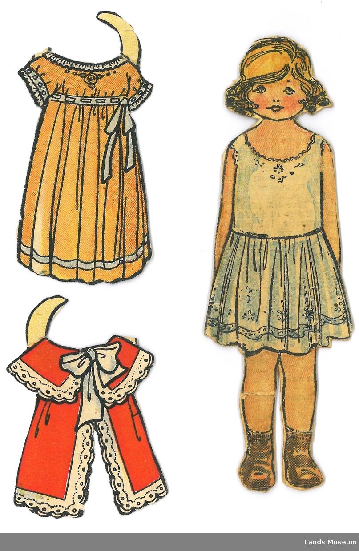 Dukke med to kjoler, klipp ut frå avis/ukeblad. Dukken er montert på papp.  A- papirdukke, 13 x 4,5 cm B- kjole, orange, 6 x 4 cm C- kappe, rød 5 x 4 cm