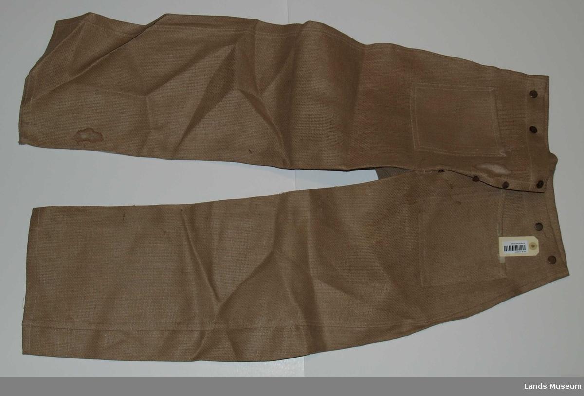 Bukse i kypertvevet stoff av papirtråd. Slike klær ble laget under krigen 1940-45. De var nærmest ubrukelige og tålte ikke vann. Denne buksa er ikkje brukt.