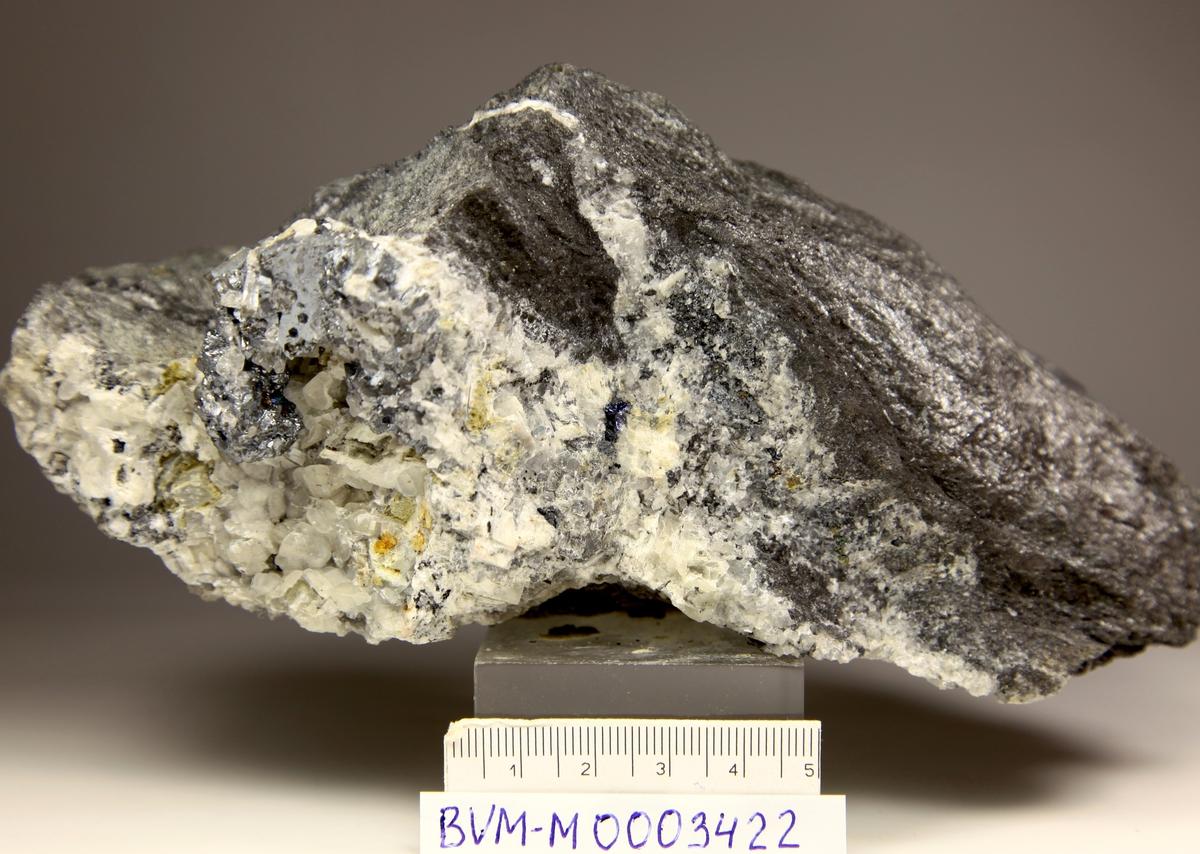Argentitt, massiv, frisk med små bergkrystaller. Se BVM 3425. Kalsittåre med druse med kalsitt + kvarts, cp på bergart med mye glimmer.