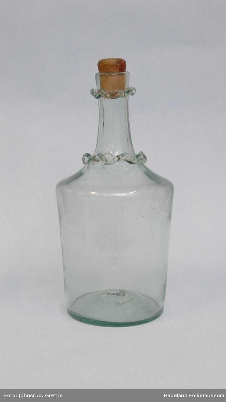 Flaske av grønlig glass. To bølgete ringer rundt halsen. Trekork.