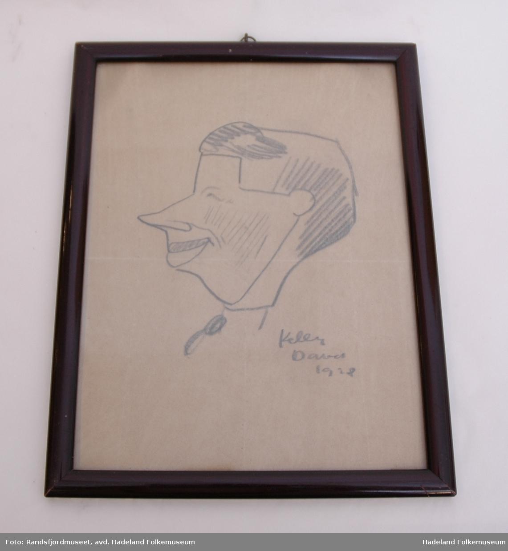 Høydeformat. Blyanttegning (portrett/karikatur) på gulnet papir. I Glass og ramme. Rammen er av mørk tresort, lakkert. Rammen er pålimt et svart, mønstret papir på baksiden