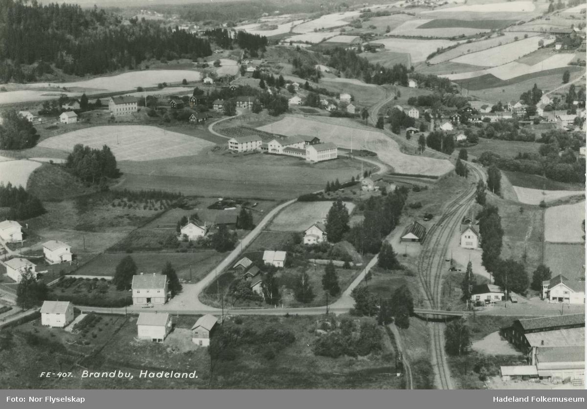 Brandbu sentrum vest. Bak fra venstre: Vesttoppland folkehøyskole, Skogskolen og Augedals bro. Foran fra venstre: Bentestuen butikken, Brandbu jernbanestasjon, Frogner butikken