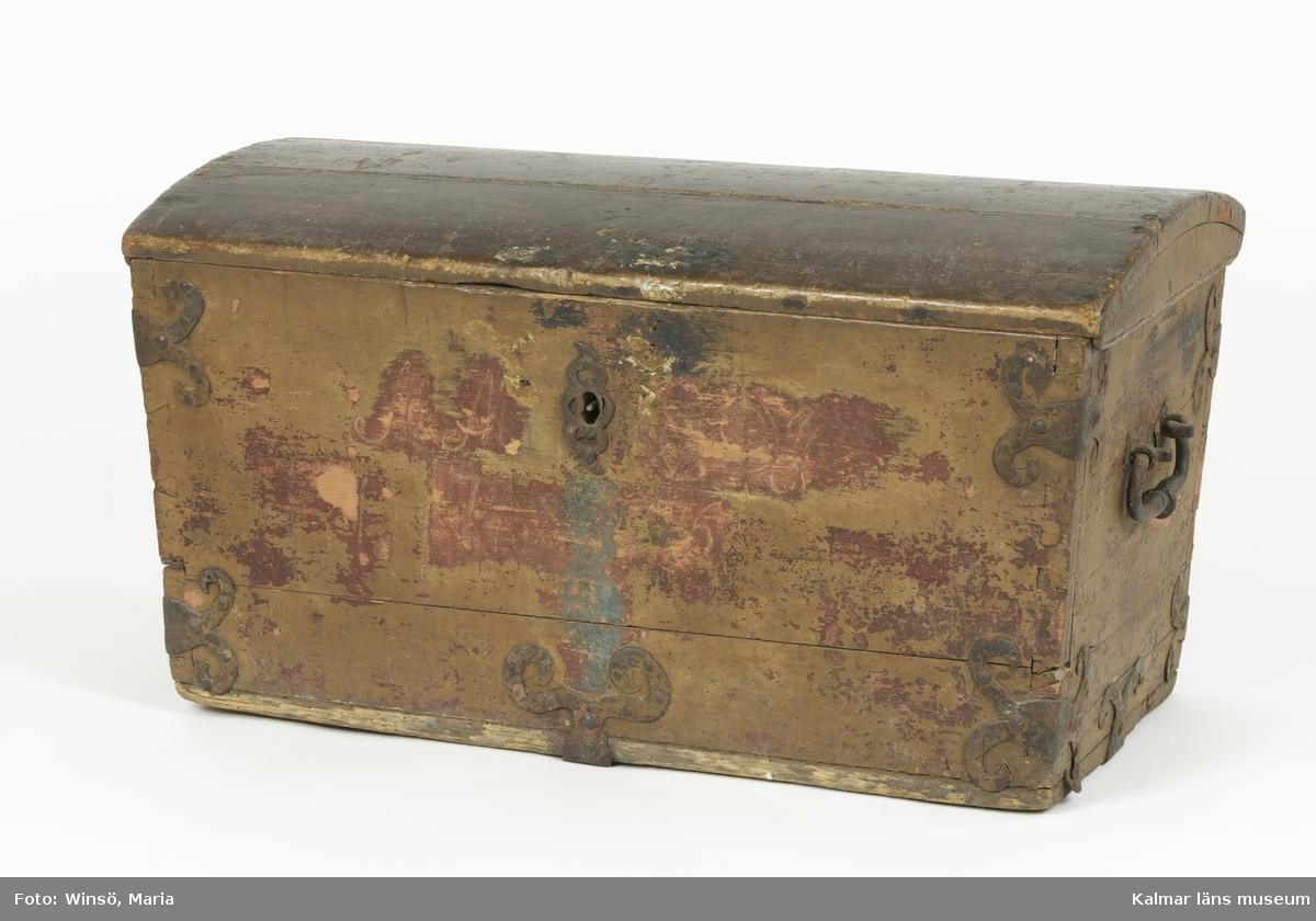 KLM 9850. Kista. Trä, järn. Bemålad kista med välvt lock. Hörnen är sinkade och lockets gavlar är fästa med träplugg i lockets ovansida. Handtag, gångjärn, beslag och nyckelskylt av järn. Två beslag i varje hörn och likadana beslag i nederdelen av kistans gavlar och front. På baksidan går ett bandgångjärn som på locket är fäst på insidan. Kistan har ursprungligen varit målad i rött med en målad påskrift i vitt, M.M.E.O.H 1775. Ursprunglig färg och måleri är framskrapat på delar av fronten. Övriga sidor har senare bemålning i brunt. Kistan är låst och saknar nyckel.