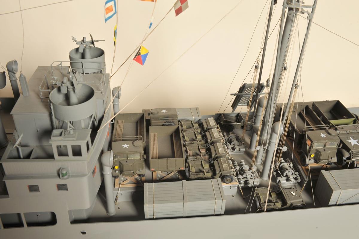 """Modell av D/S """"Ravnefjell"""", malt grå som hun var under 2.verdenskrig. Med bestykkning og dekkslast. Rederiets merke på skorsteinen. Overmalt i 1976 av modellbygger Erling Holthe da modellen ble endret til utseendet under 2. verdenskrig. Skala :  1:48"""