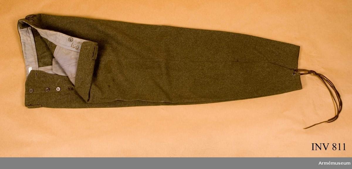 Stl D 96. Av gråbrungrön kommiss. Vida över säte och knän och  avsmalnar nedanför knäet. Försedda med tillslutningsanordning  nedtill på byxbenen och hålls ihop av två läderremmar 2 mm breda  och ett öljetterat hål. I midjan finns slejfar och dessutom fyra  tennknappar för att fästa hängslen i. Fickorna är insydda och  snedställda.