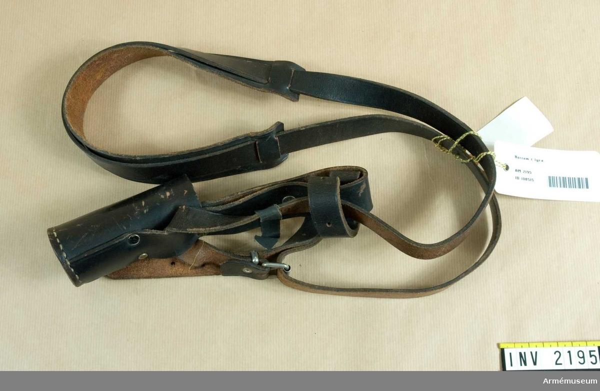 """Samhörande nr är 2192-2195.Bärrem t lyra.Av svart läder. En """"tuta"""", 105 mm hög, för instrumentets stång som vilar i denna då lyran bäres med rem runt halsen? För att inte skava är remmen förstärkt i nacken (?) med en något bredare skinnbit som trätts på remmen."""