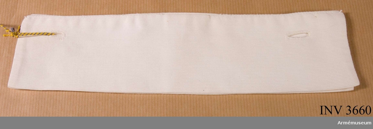 Manschett till lottaklänning i bomull, grå, SLK. Sydd dubbel i vit piké. Två handsydda knapphål i vardera långsidas yttre kant. Skall knäppas på klänningens manschettknappar. Det vill säga den undre knäppningen. Längd 195-215 mm, bredd 57 mm.