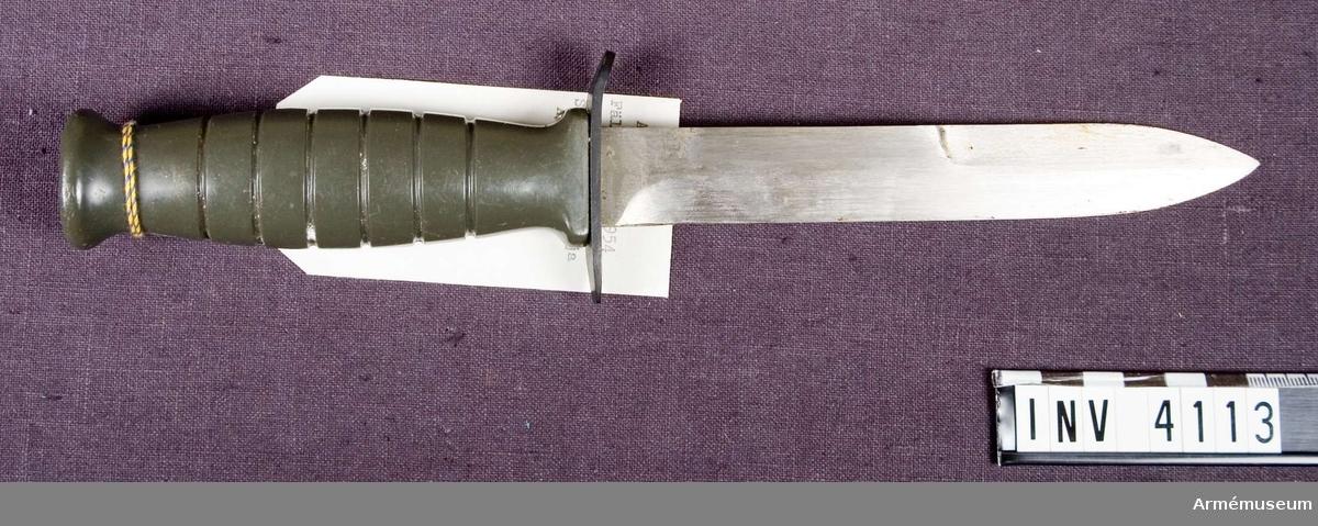Samhörande nr är 4113-4114.Fältkniv fm/1954, försöksmodell.Kort klinga utan blodskåra; bredd vid fästet: 23 mm. Egg på halva ryggen. Fäste av plast. Märkt på parerstången.