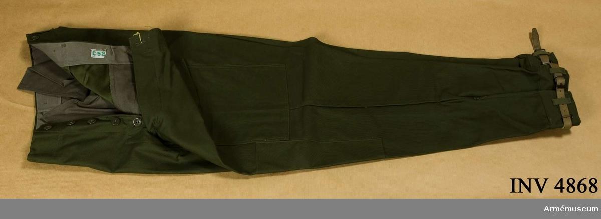 Skick som nya. Storlek: C 52. Fältbyxor m/1959 I 1. Tillverkade av olivgrönt tyg, har fasta damasker och två framfickor, en bakficka och hällor för bälte,  samt två benfickor. Byxorna har jylfknäppning och förstärkning  Över knäna och förutom hällor för bälte knappar för hängsle. Damasken tillsluts med läderrem. UNIA 1977 6:101-112.  Samhörande gåva: AM.04860-4925-4964.