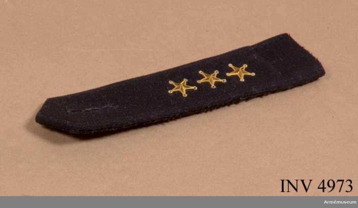 Av mörkblått (svart) kläde med knapphål / gradbeteckning för kapten = tre guldstjärnor m/1858.