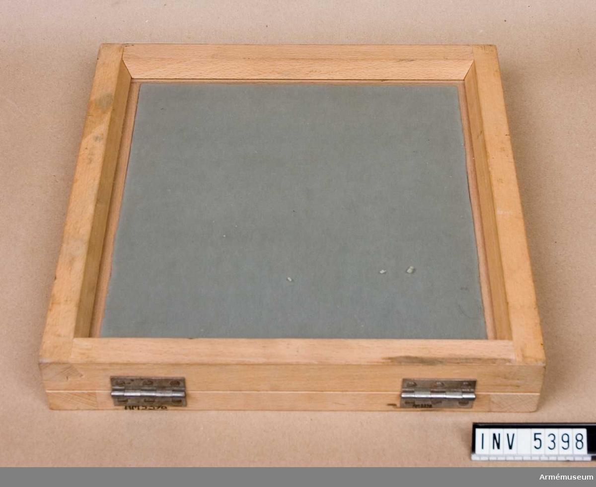 Kontaktkopieringsram för flygfilm M 3821-201.Består av två glasskivor i en gul ram av trä med gångjärn. Ganska gott skick. Märkt på baksidan: M 3831-201 .Ingår i fotomaterielsats 6 låda 3, AM 5395.