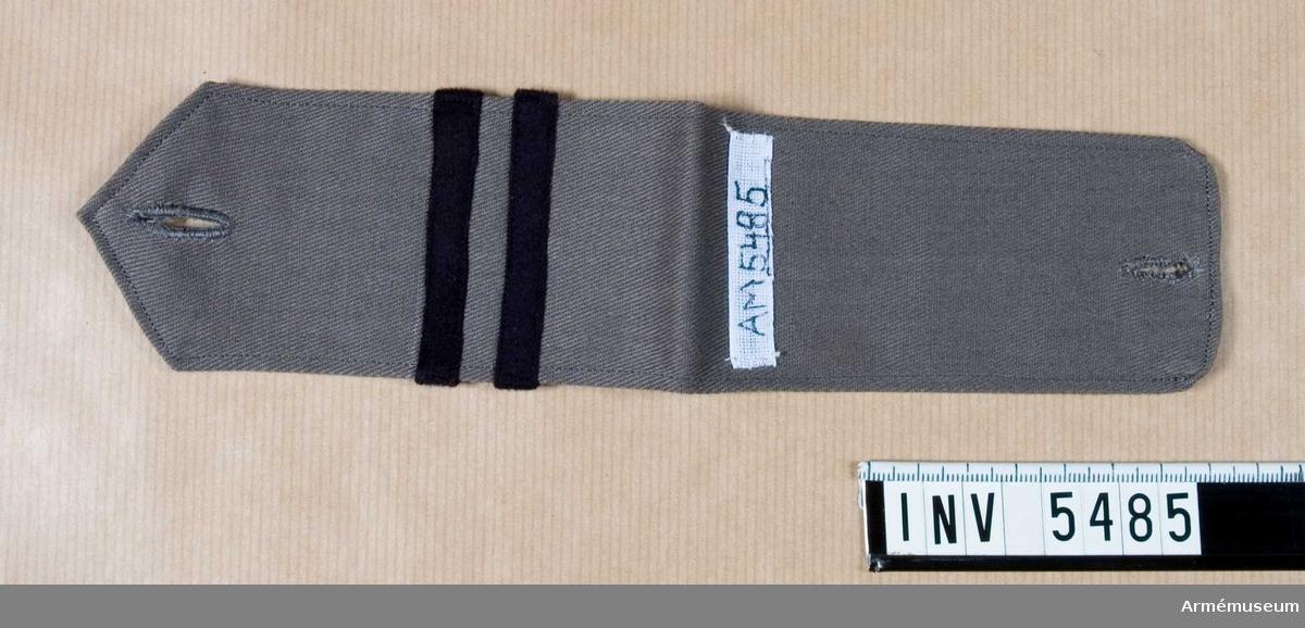 Av grått bomullstyg m spets och knapphål vid axeln. Två mörkblå gradbeteckningsband (motsvarande korprals tjänsteställning), 8 mm breda. Placerade på tvären, det första 30 mm från vikningen.Gåva av E Lindberg, f Bokelund, Halmstad. Se AM 3635.