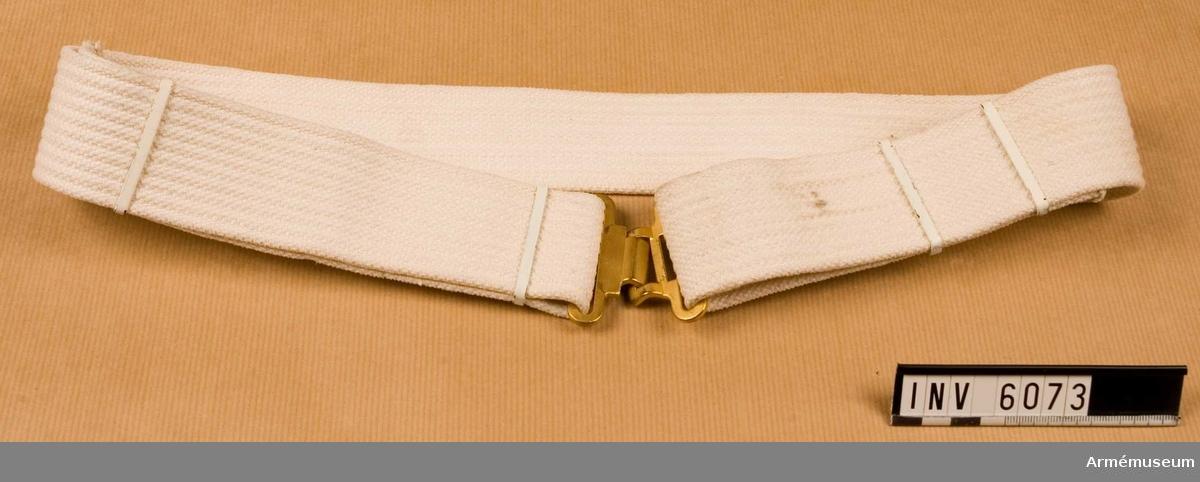 """Livrem m/1954 för musikavdelning/vaktdräkt. Av vitt textilband m mattförgyllt spänne. Källa: Bo Ancker """"Vaktparaden kommer"""". Uni A 6:502.  Samhörande nr är 5828-5899, 6000-6099, 6200-6212"""