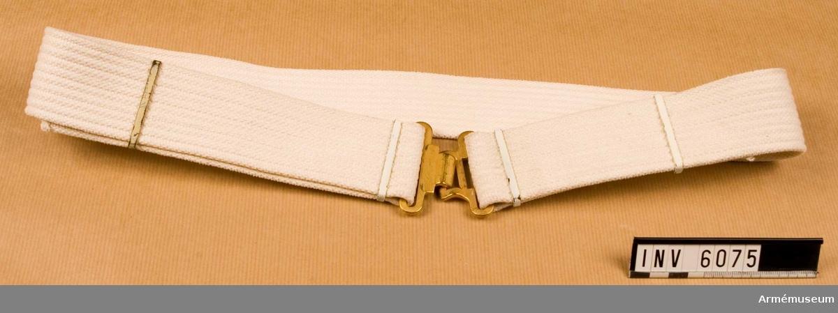 """Livrem m/1954 för musikavdelning/vaktdräkt. Av vitt textilband m mattförgyllt spänne. Källa: Bo Ancker """"Vaktparaden kommer"""". Uni A 6:502.  Samhörande nr är 5828-5899, 6000-6099, 6200-6212."""
