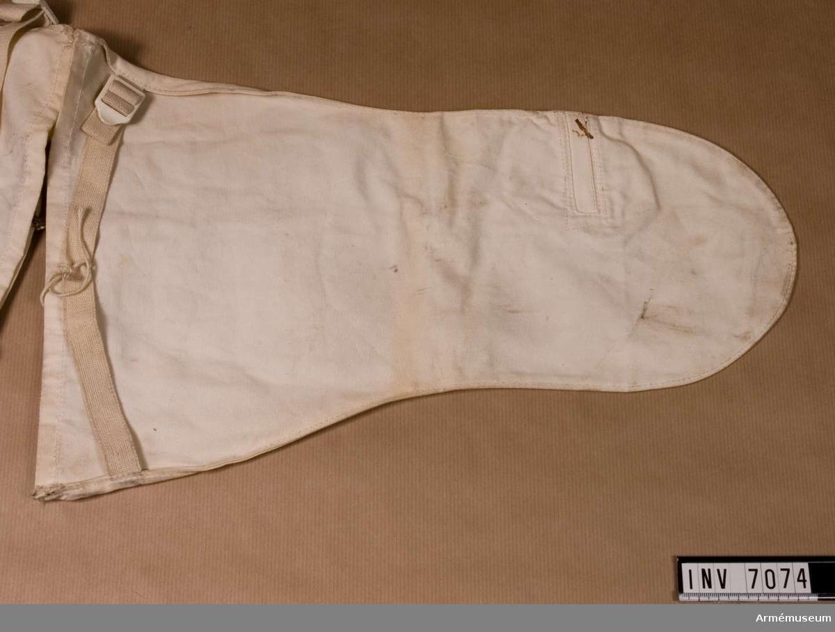 Handske t snödräkt. Av vit poplin och försedd med skaft med åtdragsrem, tumme och hål för skjutfingret.