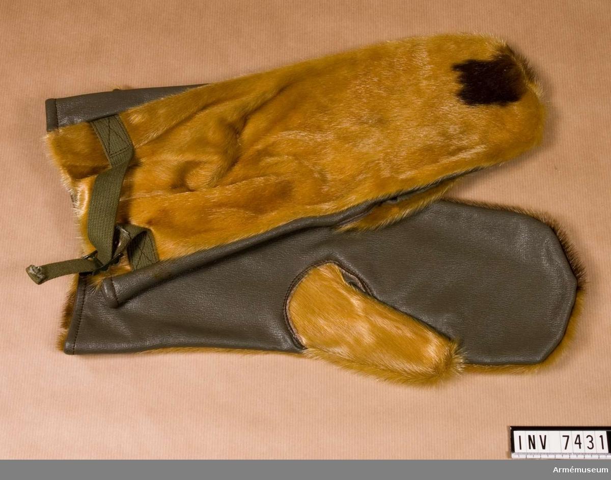 """Tumhandskar med sälskinn på ovansidan av handen och på tummen. För övrigt grå plast som är """"ruggad"""" på avigsidan, åtdragbar med grönt textilband. Färg gulbrun och grå E Q."""