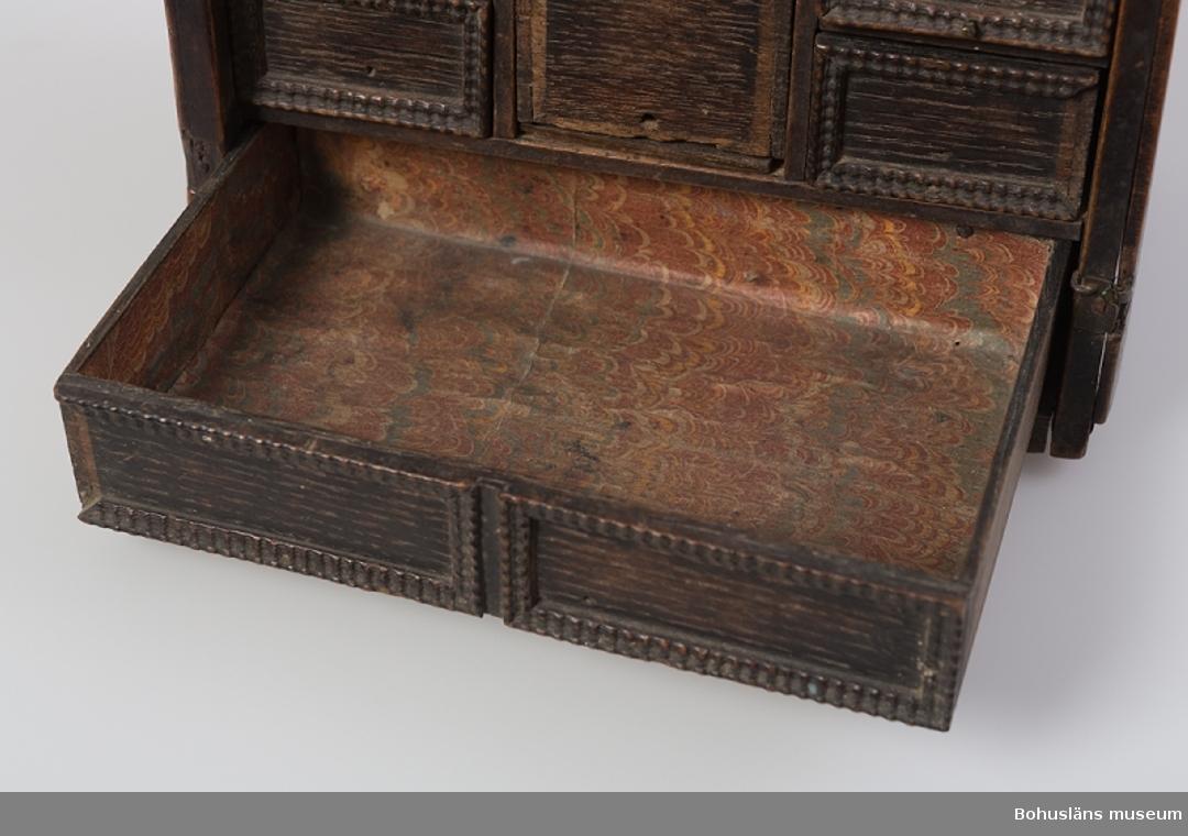 Mindre kryddskåp i bonad ekfaner med sju symmetriskt placerade utdragbara lådor. Lådförstyckena dekorerade med hopplistkanter. Skåpet är defekt. Det har haft två främre dörrar, vilka saknas, återstår tre gångjärn av mässing, varav två är trasiga. Endast krönlisten på skåpets ena övre kortsida återstår. Motsvarande lister längs skåpets nederkanter saknas. Blindträ av furu med kraftigt ekfaner på ovansidan och kortsidorna. Lådorna är tillverkade av ek. Både skåp och lådor har laxade hörnsammanfogningar. Lådornas bottenstycken är limmade. Bakstycke med påtagliga spår efter hyvelskär. Den översta och understa lådan löper över skåpets hela bredd men dekorlisternas placering ger sken av att det är två lådor. Den mittersta lådan är extra hög och här fattas dekorkanterna och den har en lossnad lådbotten. En av de små lådorna saknar botten. Lådorna är invändigt klädda med marmorerat papper av 1700-talstyp i rött, blått och gult.  På skåpets ovansida sitter ett smitt bärhandtag med dekordel på mitten av mässing, handtagets infästningar har dekorklippta mässingsplattor. På baksidan inskuren märkning: EEG 1674. Enligt äldre uppgift kommer skåpet troligen från Bohuslän.  Ur handskrivna katalogen 1957-1958: Kryddskåp Av ek o fur. L 18, H.16, Dj, 11 cm; m. 7 lådor; luckor fram till saknas; på baksidan: EEG 1674. a)= Skåpet; b-h) = lådorna. Trol. fr. Bohusl. Nr 100e saknas botten.