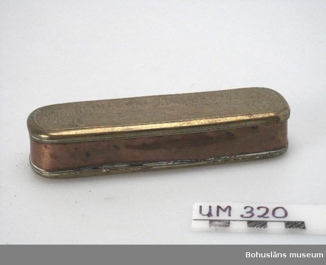 Ur handskrivna katalogen 1957-1958: Tobaksdosa Bottenmått. 16,5 x 5 H: 3,0. Mässing. Lock o botten figurmotiv. Föremålet helt.  Lappkatalog: 95