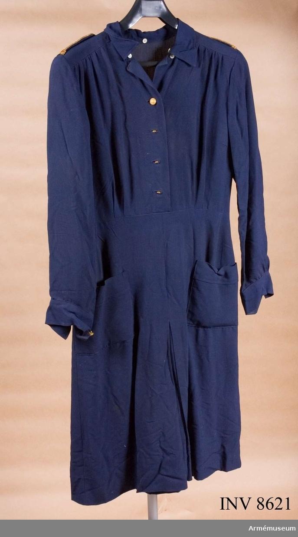 Sydd i mörkblått bomullstyg. Har långa ärmar med enkel manschett knäppt med en uniformsknapp av storlek 3. Har livsöm och knäpps upptill med fyra uniformsknappar av storlek 3 i enkel rad. Kjolen har motveck fram och baktill och är försedd med två utanpåfickor. Till axelsömmen fastsydda 40 mm breda axelklaffar av samma tyg som klänningen och knäppes med uniformsknapp storlek 3. Vid axelklaffens bas ett 13 mm brett guldband och runt kanterna ytterst en guldgalon och innanför den en blå silkegalon. Alla knapparna på klänningen är av marinens modell m/1878, tillverkare Sporrong. Har löst skärp, 28 mm brett med osynlig knäppning, av samma tyg som klänningen. Klänningen har lösa vita manschetter och krage. Källa UNI FL 1963 977.