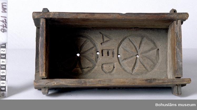 """503 Kön KVINNA   Rektangulär ostform med fyra gavlar ihopfogade med tappar och sprintar. Botten har karvsnitt med två rosetter och """"AED"""" inskuret samt fyra avrinningshål. Sprucken längsmed och sekundärt spikad. En lång- och en kortsida är nedslitna. Litt; Ränk, Gustav, """"Från mjölk till ost"""", Berlingska boktryckeriet, Lund 1966. 990 Omkatalogiserat 1996-05-15 AN  Ur handskrivna katalogen 1957-1958: Ostform, fyrkantig. Mått: 28 x 16 x 12 cm bottenbrädan mönstr. 4 genomg. hål, jämte: """"AED"""", (spukad); i övr. fogad m. tapp o. sprint. Ngt. trasig.  Lappkatalog: 53"""
