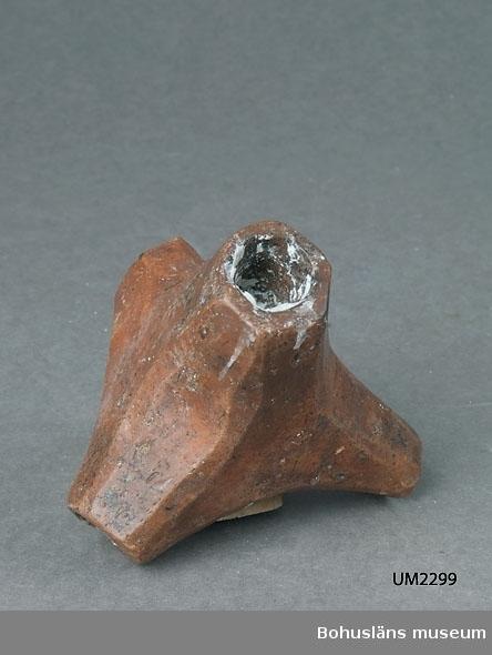 Ur handskrivna katalogen 1957-1958: Ljusstake av bränd lera Trefotad stake. H: 9,5. Något sönder vid fötterna.  Lappkatalog: 90