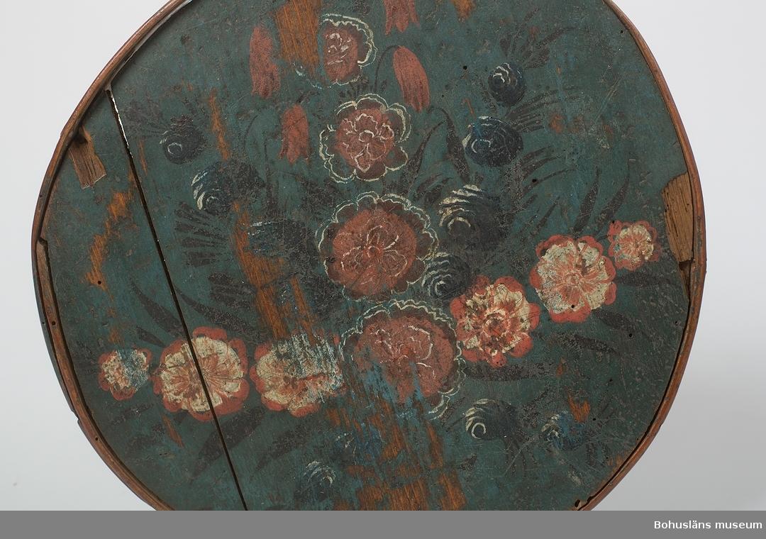 """Rund med lock, ihopfogad med kedjestygn i svepet. Blå bottenfärg och dekor i mörkare blått, svart, rött och vitt. Locket har blomsterarrangemang med röda rosor samt röd/vita och blå blommor av okänd sort. Färgen är något sliten upptill. Nedre delen har texten """"B.A.D 1805"""" i vitt med en blomsterkrans runtom. Locket har mörknat och antagit en grön nyans. I släpljus kan man se en punktmönstrad dekor på delar lockets plana yta.   Trolig förvaring för bindmössa, nipper, schal m.m. Se bild i Lychou, Kerstin, Hemslöjd & Folkkonst i Bohuslän, Warne förlag AB, Partille 1996, sid 77. Se bild i Granlund, John, Träkärl i svepteknik, Nordiska Museets handlingar 12, Stockholm 1940, sid. 194 fig. 136. Neg.nr UMFF 446, Kerstin Lychous dia 531  Ur handskrivna katalogen 1957-1958: Fonask""""BAD 1805"""" Rund. Diam.: 27-28. H: 16,5. Blågrön med blomdekor. Skadad, bl. a. botten. Maskhål. Lyckorna, Bohusl.  Lappkatalog: 84"""
