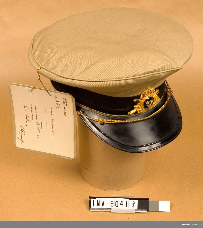 Tillverkad av beigefärgat bomullstyg s k khaki. Har svart lackerad skärm och svart mössband. På sidornas liten knapp av generalstabens modell i guld och framtill mössmärke för officer till skärmmössa m/1952 och m/1960 (1961). Mössrem av guldtråd för kompani och plutonbefäl. Storlek 57.