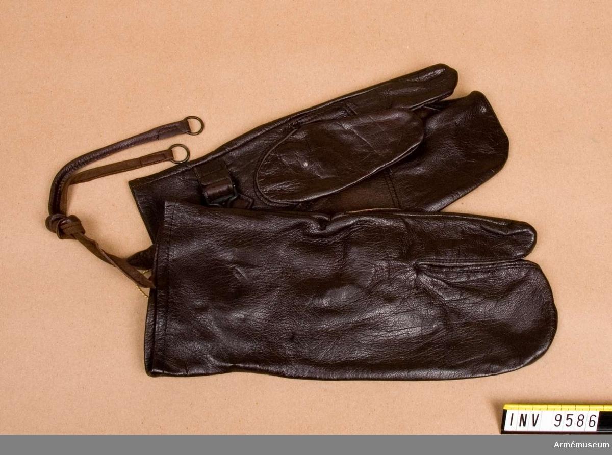 Skjuthandskar. Av brunt skinn med tumme och pekfiner fria och med åtdragsrem på insidan av handloven. Ett par. Gåva från FMV i Solna.