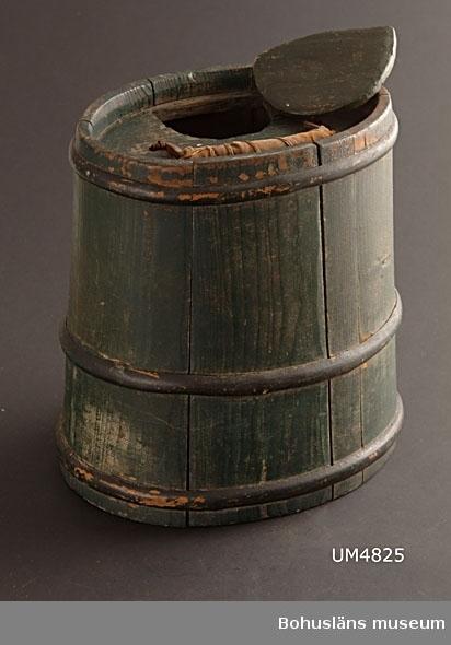 Ovalt upprättstående laggkärl. Det är något avsmalnande upptill. Stavarna hålls ihop med hjälp av tre horisontella träslåar. Upptill finns ett lock med ett handtag av järn mittpå. Handtaget är lindat med en bit bomullstyg för att underlätta när man bär. Locket har en halvcirkelformad öppning i kanten, vilken stängs med ett lös litet lock i likadan form. Kärlet är målat med mörkt grön färg. Träslåarna är målade i svart.  UM4764 är ett samma föremål (det finns en äldre märkning målad med svart färg undertill).  Litt.; Keyland, Nils, Svensk Allmogekost II, Svenska Teknologföreningens förlag, Stockholm, 1919, s. 86-96.  Ur handskrivna katalogen 1957-1958: Brännvinskagge grön m handtag Bottenmått: 26 x 19 H: 28 Oval botten. Trä. Föremålet helt. Se UM4764.  Lappkatalog: 52