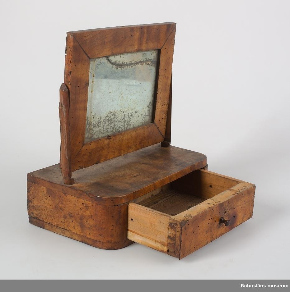 Ur handskrivna katalogen 1957-1958: Rakspegel med låda H.: 30 cm. Lådans mått: 19,2 x 15,5 x 5,4 cm. Spegelns mått (inkl. ram): 23,8 x 20,2 cm. Maskhål.  Lappkatalog: 94