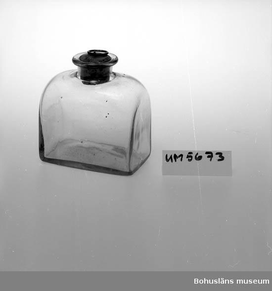 Föremålet visas i basutställningen Uddevalla genom tiderna, Bohusläns museum, Uddevalla.  Ur handskrivna katalogen 1957-1958: Brännvinsflaska Bottenmått: 10 x 6,7 H.: 11,5. Fyrsidig flaska. Hel. Försedd med kork.  Lappkatalog: 61