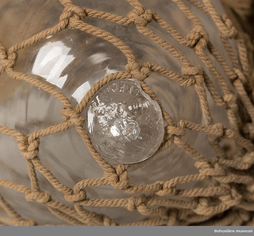 """Ofärgade glaskulor med nät runt om. Puntelmärken.                      På puntelmärkena är det inpressat delar av texten:""""C A LINDGREN & CO   PUNSCH STOCKHOLM"""".  Nätet är söndrigt runt två av kulorna.              Omkatalogiserat 1996-04-01 GH."""