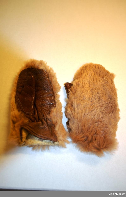 Barnekåpe i lys,brun tweed med brune knapper. Foret med blomstrete stoff. Hatt i brun fløyel. Rutete skjerf og skinnvotter.