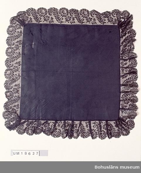 """Kvadratisk svart schalett av sidenrips. Med 11 cm bred maskintillver- kad spets fastsydd för hand ytterst. Spetsen är lagd i veck vid hörnen och längs två av sidorna, men slät längs två sidor. Två sidor av spetkanten mot tygets avigsida (gör schaletten vändbar?). Schaletten har tillhört Hilma, Samuelsson, Ulebergshamn, f. 1862 d. 1923, stenhuggarhustru. Se bilaga för uppgifter om släktskapsförhållande mellan brukare och givare. Hål i två av spetsens hörn, spetsen för övrigt i gott skick. Bristningar i tyget. Något fläckig.  Litt; Håkansson, Elin, Sidenhalsdukens bruk och tillverkning ur """"Sörmlandsbygden"""" 1933. Lewis, Katarina, Schartauansk Kvinnofromhet i tjugonde seklet, Uddevalla 1997, sid. 126. Lindvall-Nordin, Christina, Mossrosor och hjärtblomster ur Kulturens årsbok 1969, Lund. Wulfcrona-Dagel, Marie Louise, Schaletter och halskläden i Nordiska museet vävda hos K A Almgrens sidenväveri i Stockholm, uppsats för fortsättningskurs i etnologi, Stockholm 1979."""