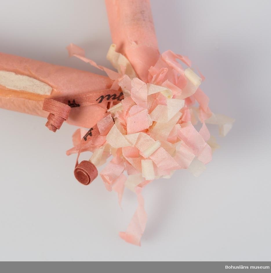"""Julgranskaramell, tre karameller lindade med rosa och vitt """"krusat"""" silkepapper är hopknutna till en triangel. Prydnad avsedd för julgran. Clara Nilsson (1866-1946) var  mormor till givarna, systrarna H.H. och B.K."""