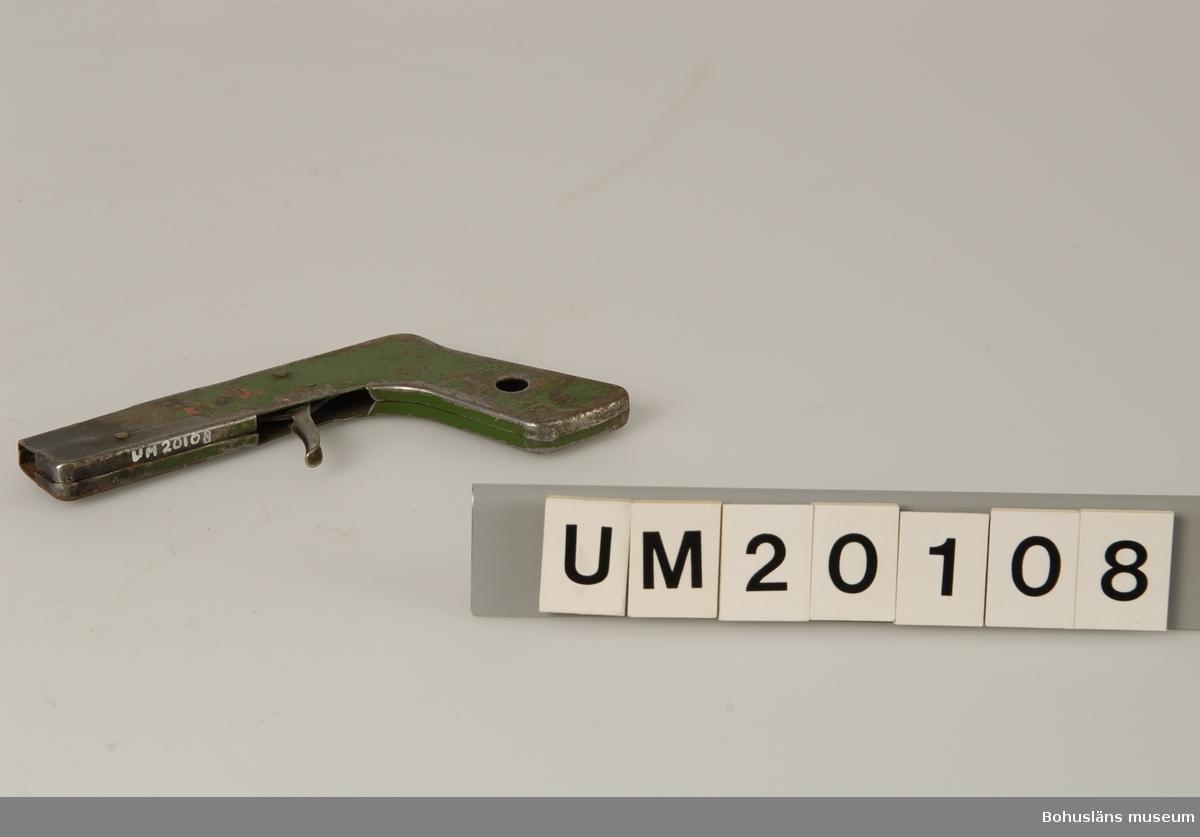 Föremålet visas i basutställningen Uddevalla genom tiderna, Bohusläns museum, Uddevalla.  410 Mått/Vikt ! TJ 1 CM 594 Landskap BOHUSLÄN  Tändaren är av pistolmodell. Grönmålad, färgen delvis bortsliten. Rostig. En mässingskruv saknas.