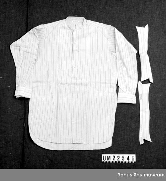 """410 Mått/Vikt ! ÄL 56 CM 594 Landskap BOHUSLÄN  2 st.likadana löskragar medföljer. Skjortan är grå med smala svarta, röda och vita ränder. Skjortan är märkt: """"Fredr.Fribergs eftr. Alb. Jakobsson Uddevalla:"""" Löskragarna märkta: """"Denna krage är tillv. enligt """"Laminex"""" metoden pat. splin. No.3291/35. Kokas ej, stärkes ej. Strykes mycket fuktig.""""  UMFF 124:12"""
